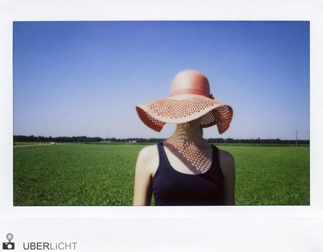 Fujifilm Instax 210 Frau mit rotem Hut auf gruenem Feld