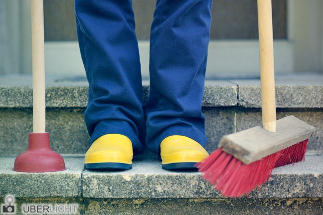 Hausmeister mit Gummistiefeln, Besen, Pömpel auf Treppe vor Haustür